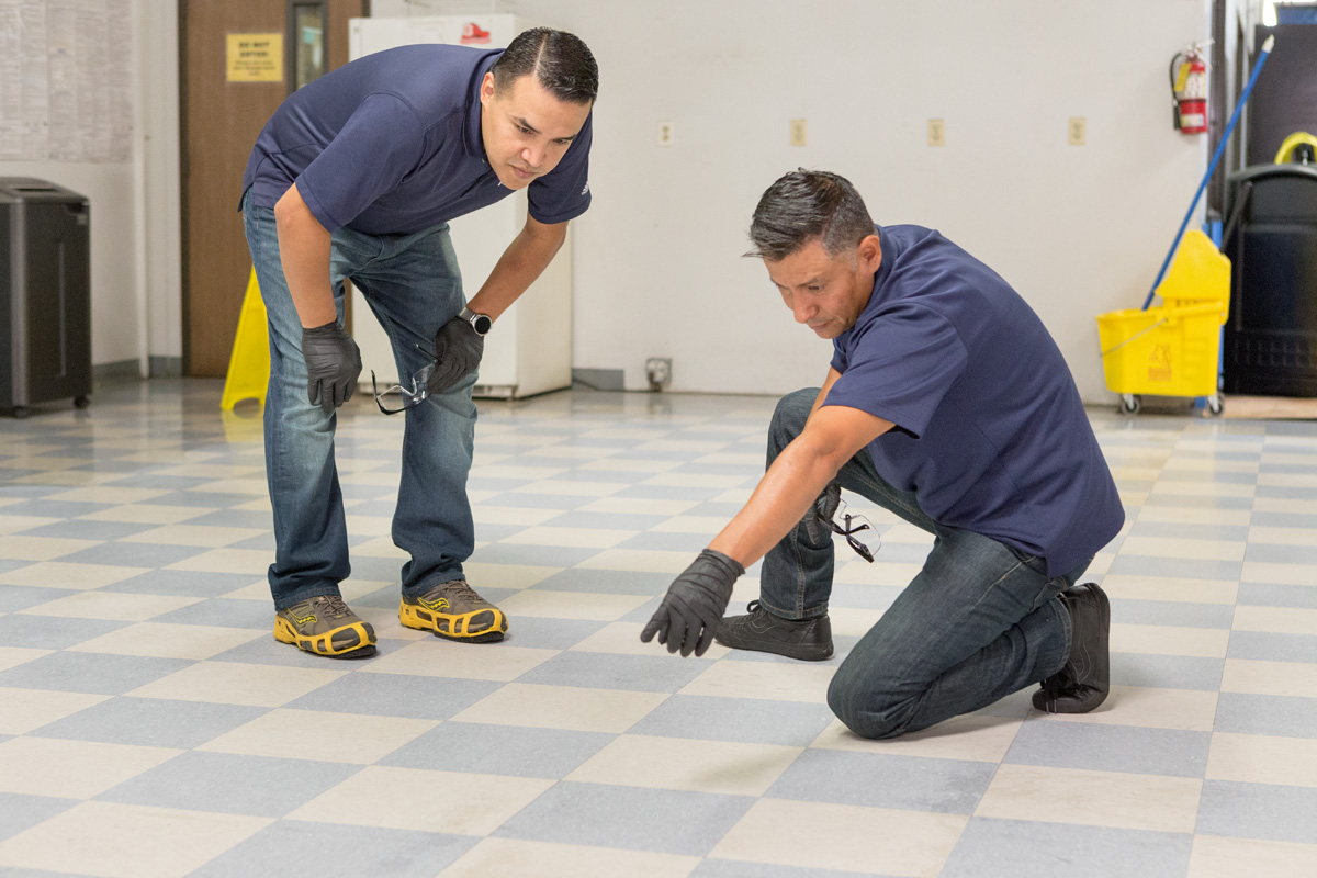 Two men inspecting a floor before finishing