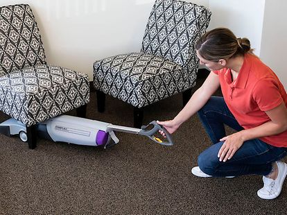 woman vacuuming under a chair
