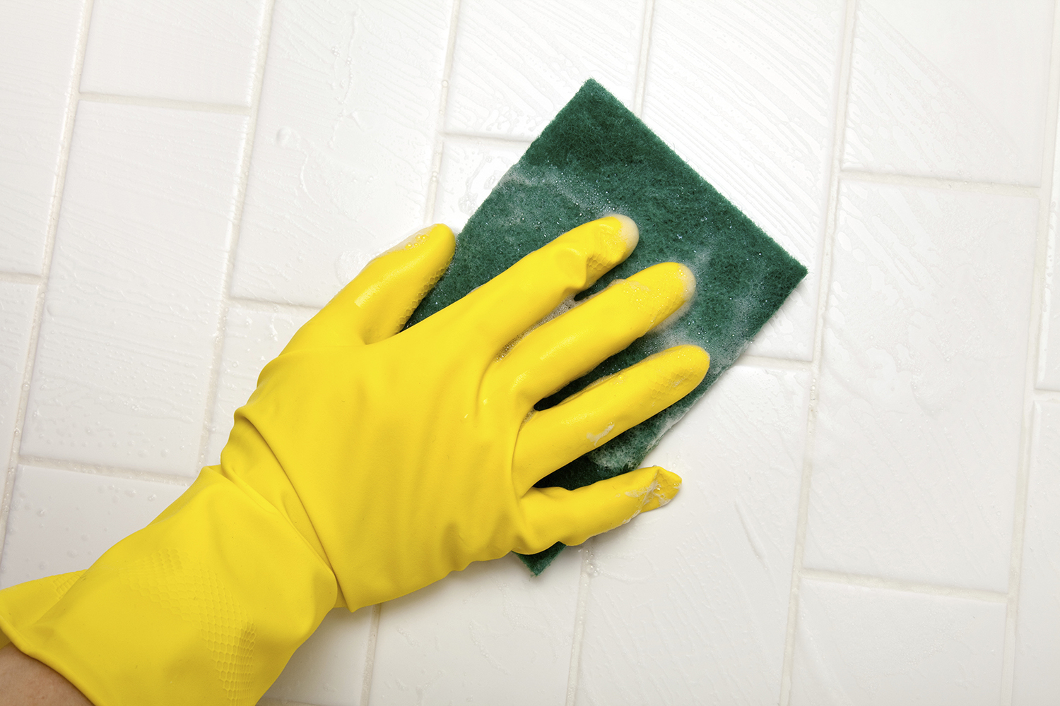 Yellow gloved hand scrubbing tile with a sponge